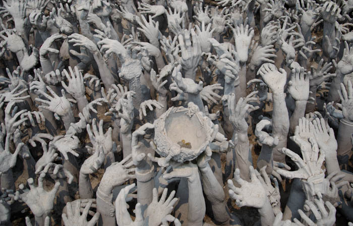 sculptures of hands coming out of the ground at the white temple in chiang rai