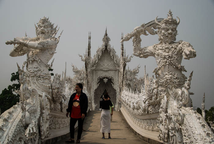 two demons guarding the bridge at the white temple in chiang rai