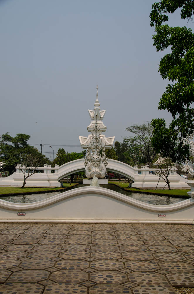 a white statue showing a dragon at white temple in chiang rai