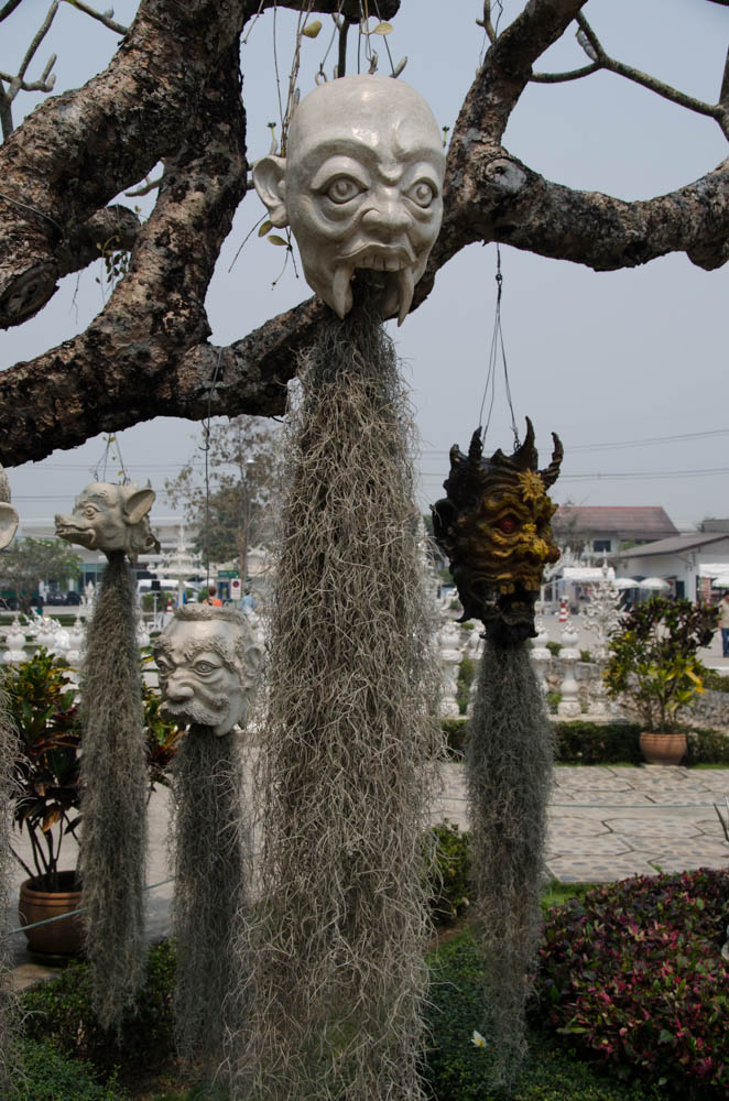a head mask hanging from a tree at the white temple in chiang rai