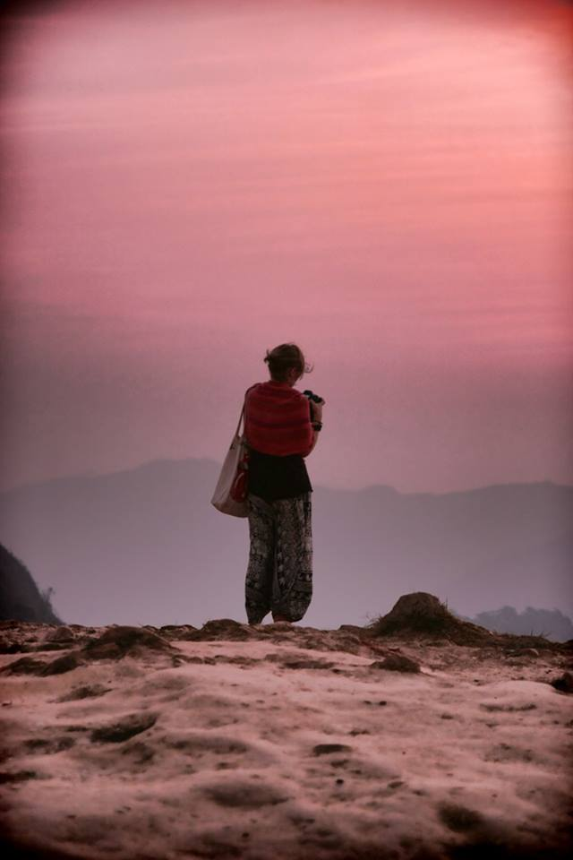 a woman with a camera standing on an edge of a mountain in thailand
