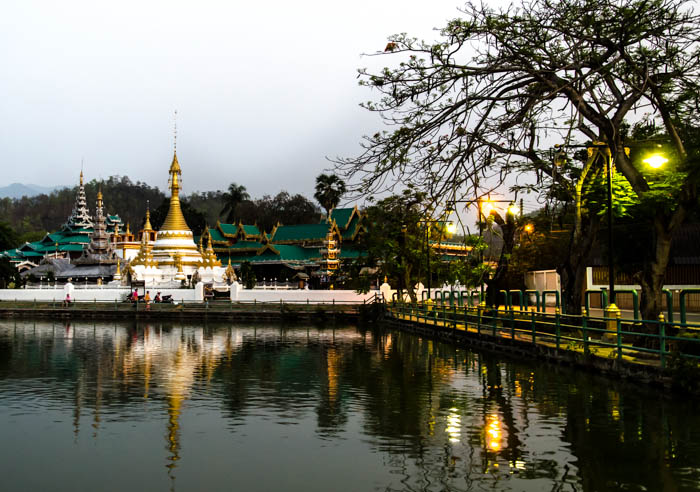 a temple complex reflecting in the water in mea hong song, thailand