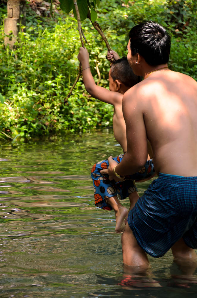 a child with his dad playing in a pool, in mean hong song, thailand