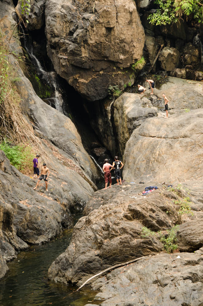 people standing near a waterfall in mea hong song, thailand