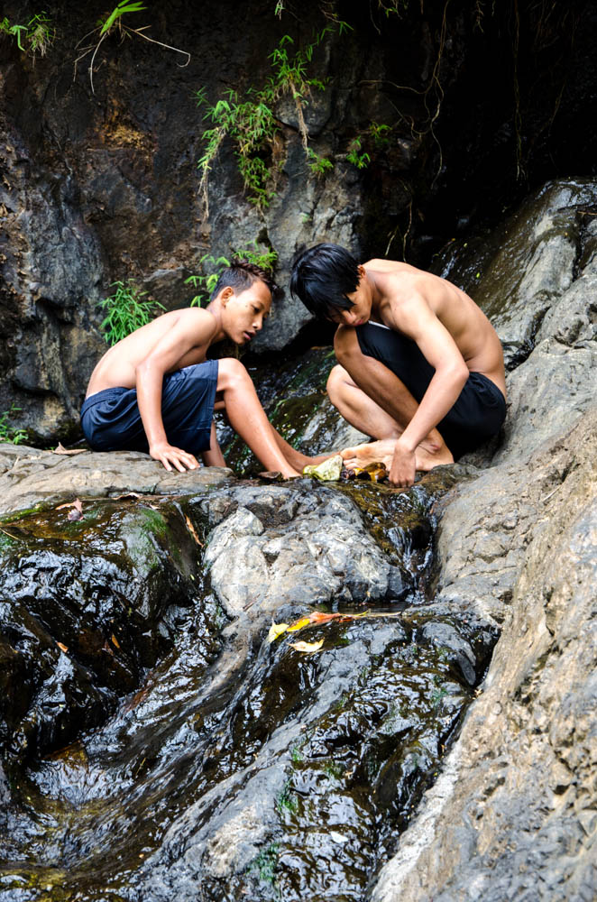 two boys playing at a waterfall in mea hong song, thailand