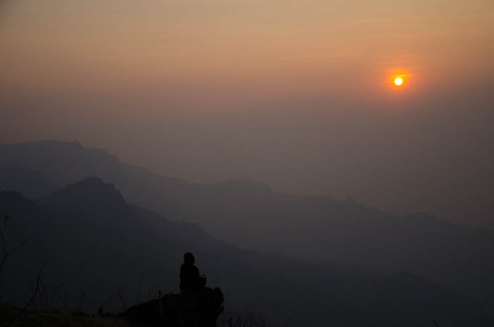 shadow of a woman sitting on the phu chi fa mountain at sunrise