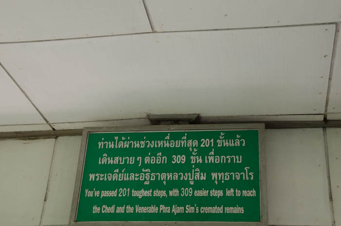 a green sign with white letters with a buddhist quote at chiang dao cave, thailand