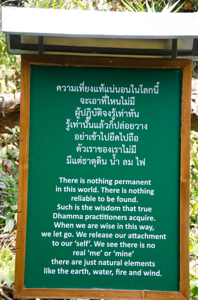 a green sign with white letters at wat po ploy, chiang dao, thailand