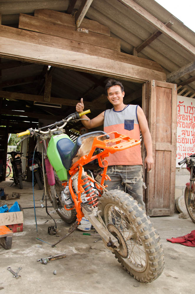a man standing at his bike in a motorbike workshop in chiang dao, thailand
