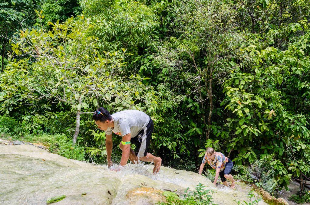 People climbing on sticky waterfall
