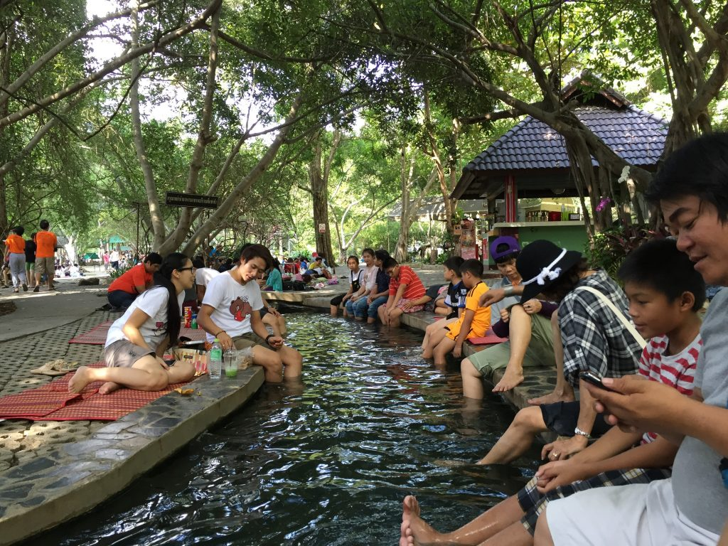 People dipping their legs in warm water from the San Kamphaeng Hot Springs