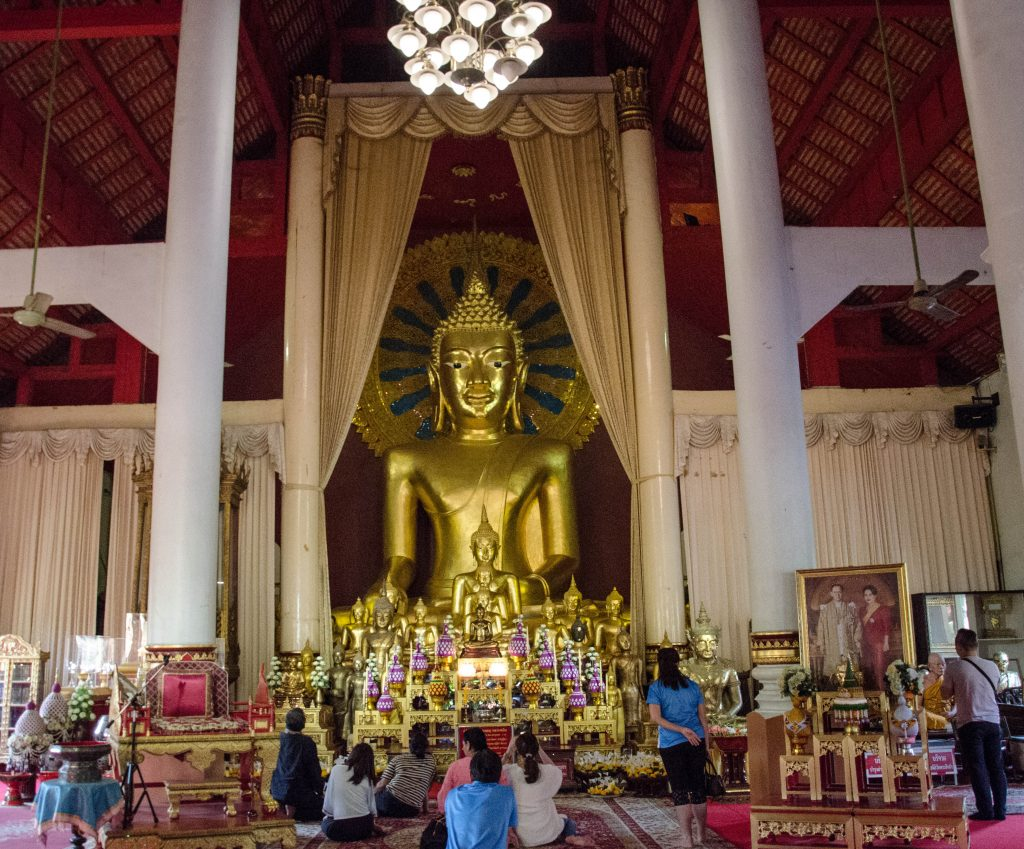 People praying in front of a golden buddha statue inside Wat Phra Singh