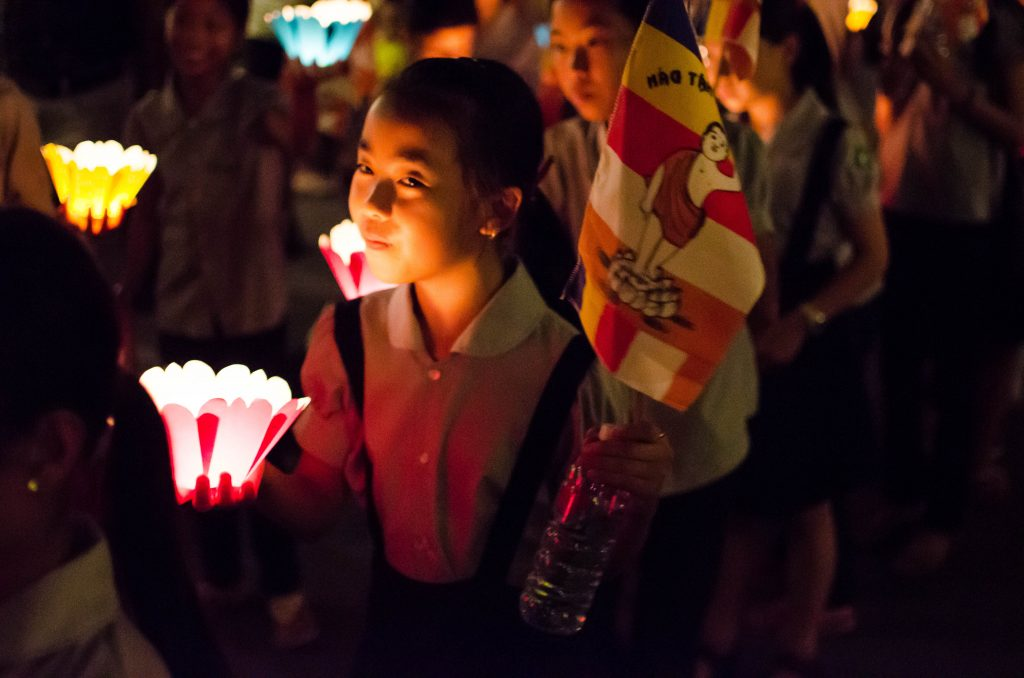 Girl with lantern at a procession during the Lantern Festival in Hoi An