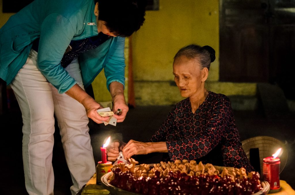 Old lady selling figurines in the streets of Hoi An