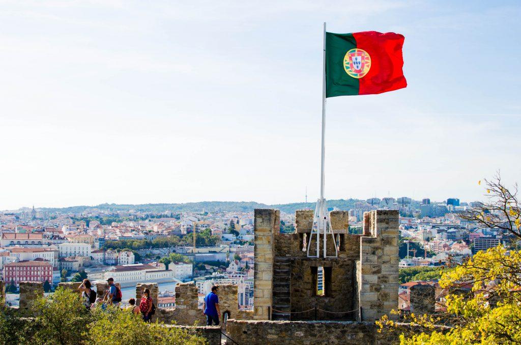 Portugalska flaga powiewa na zamku świętego jerzego w lizbonie.