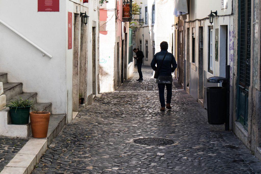 przechodnie w dzielnicy mouraria w lizbonie