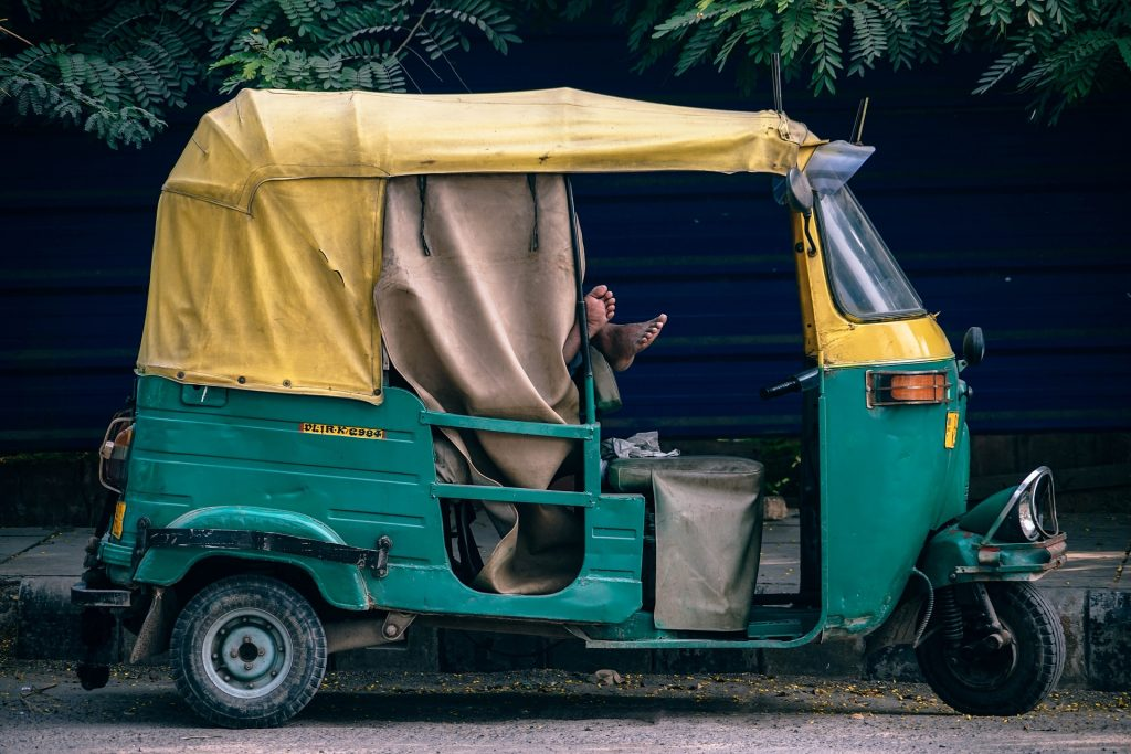 a driver sleeping in a tuk tuk