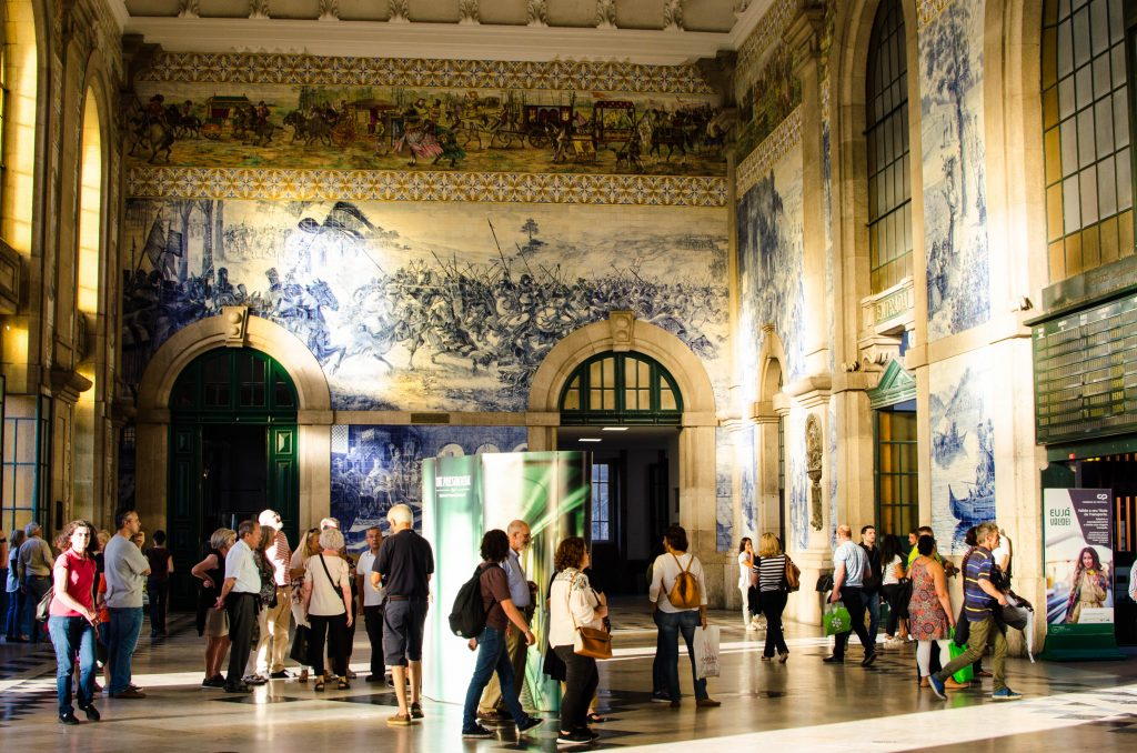 people walking in sao bento station admiring the azulejos