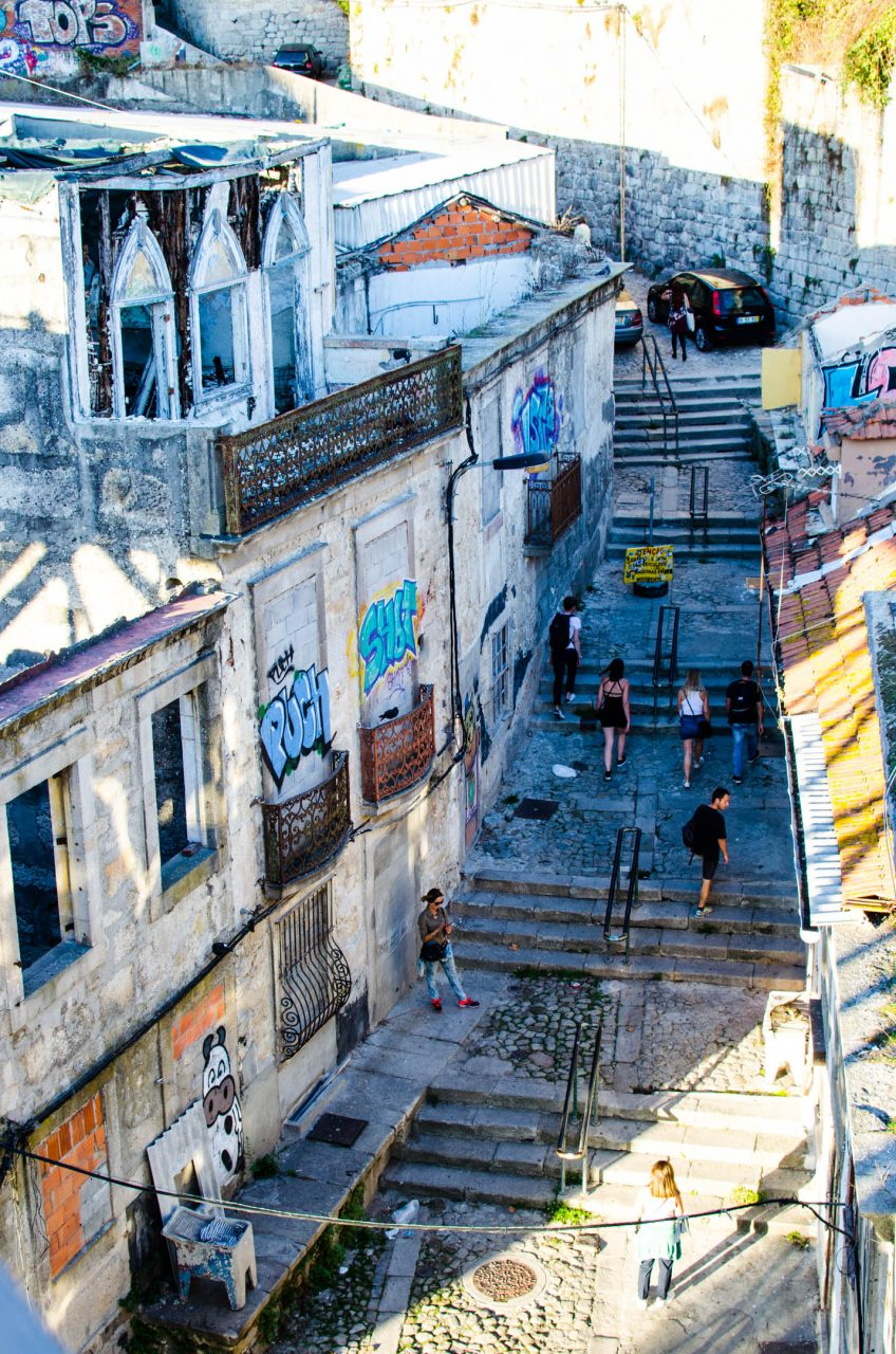 a street in porto. narrow stairs among old houses lead up the hill. people walk up the stairs in porto.