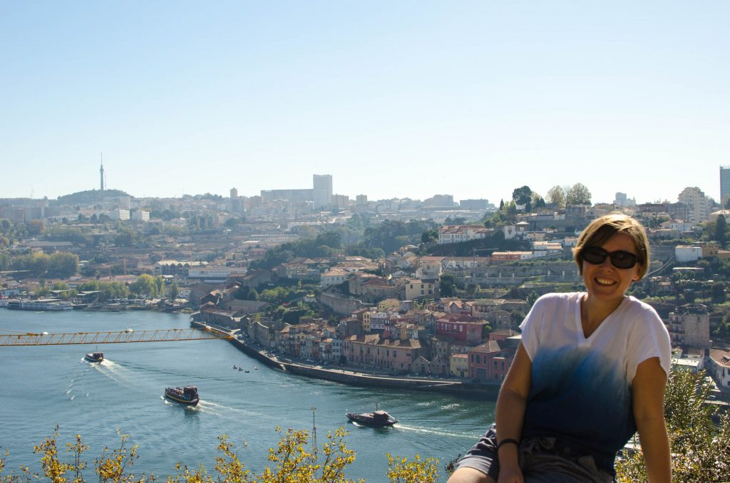 one day in porto. Joanna sits at a viewpoint in porto overlooking the river and the city.