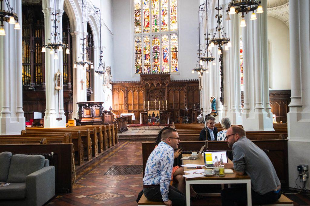 Ludzie siedza przy stoliku w Host Cafe w Londynie