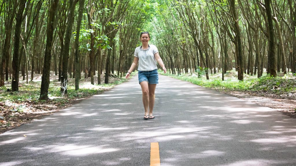 Joanna walking in rubber trees orchard khanom thailand