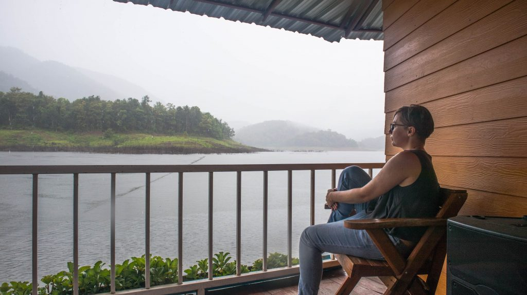 joanna horanin sits on a terrace by a lake and watches the rain