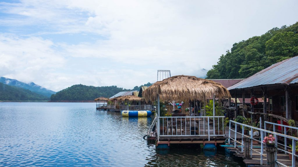 floating bungalows on mae ngat dam in thailand, bamboo terraces seen from the water