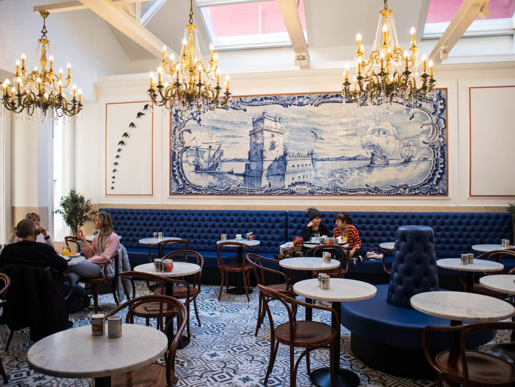 the interior of a coffee shop in lisbon with crystal chandeliers and tiles