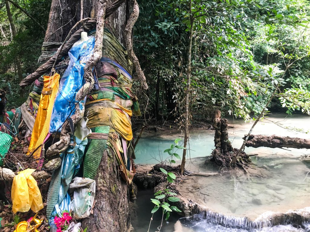 erawan waterfall colourful clothes attached to a tree with emerald water flowing