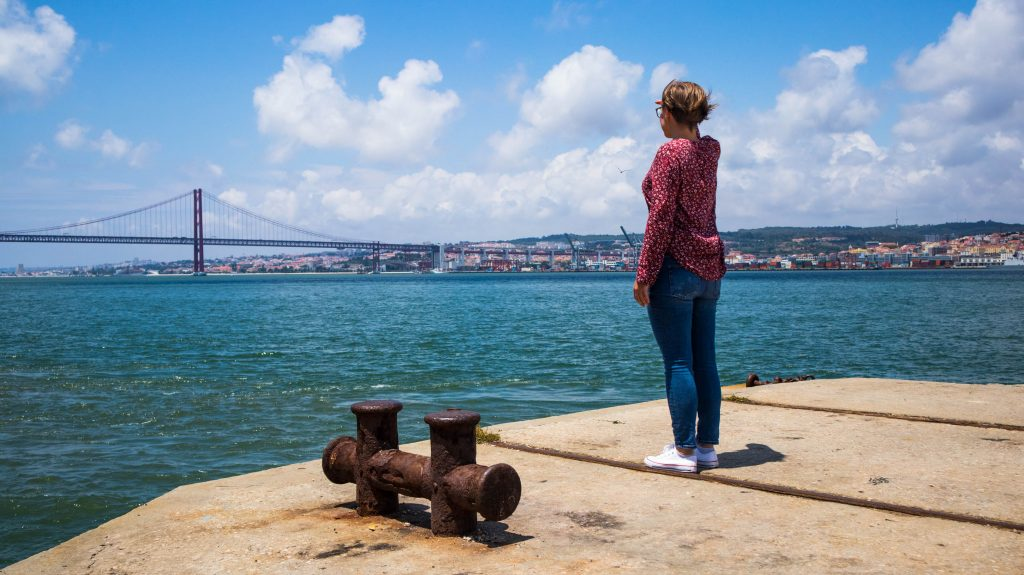 a girl standing in almada looking at the bridge in lisbon