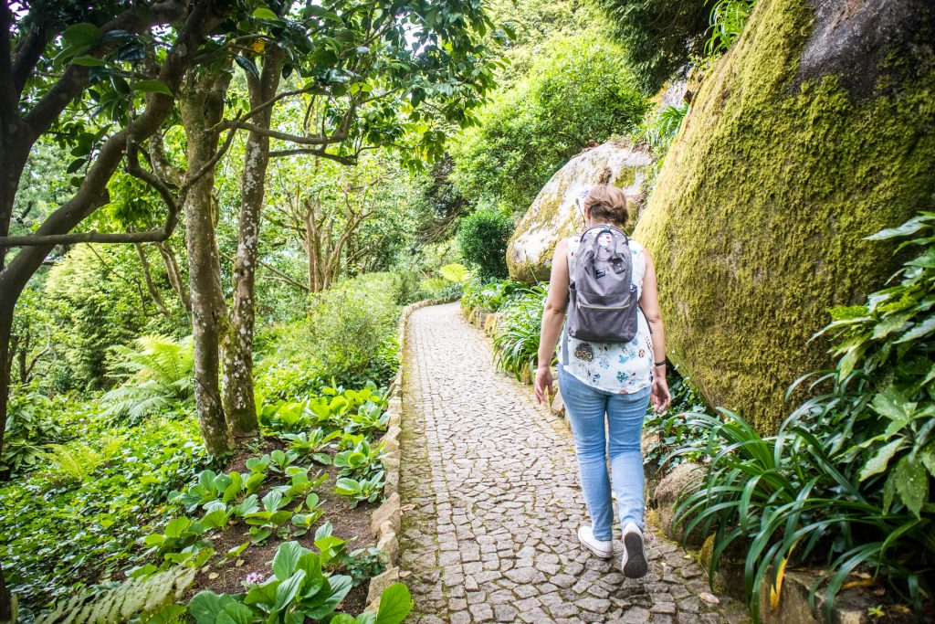 a girl walking the trail to pena place in sintra