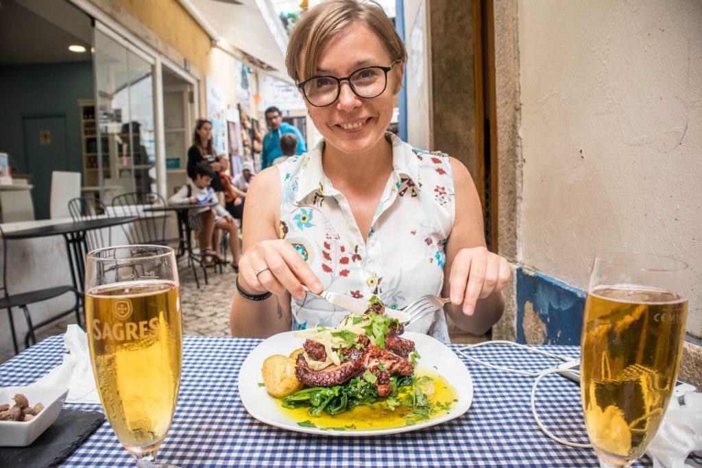 nauczycielka angielskiego online usmiecha sie jedzac osmiernice w portugalii