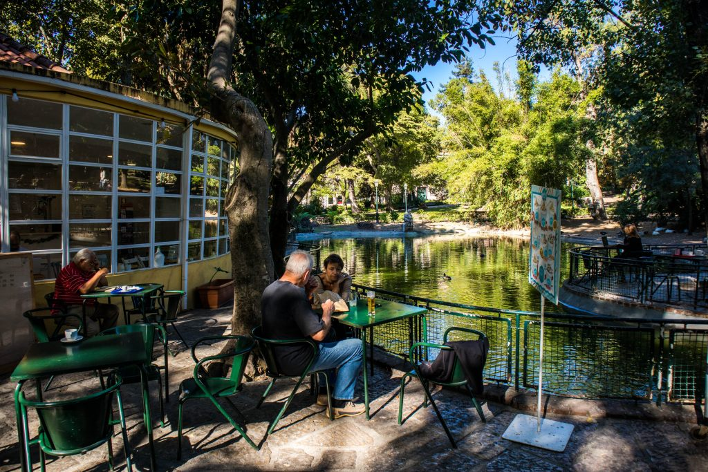 people sitting in a cafe near the pond in the estrela park, lisbon