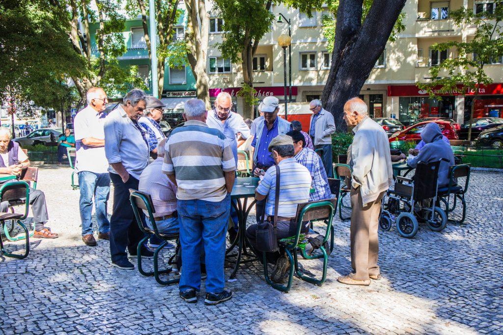 starsi mezczyzni graja w karty w parku w lizbonie