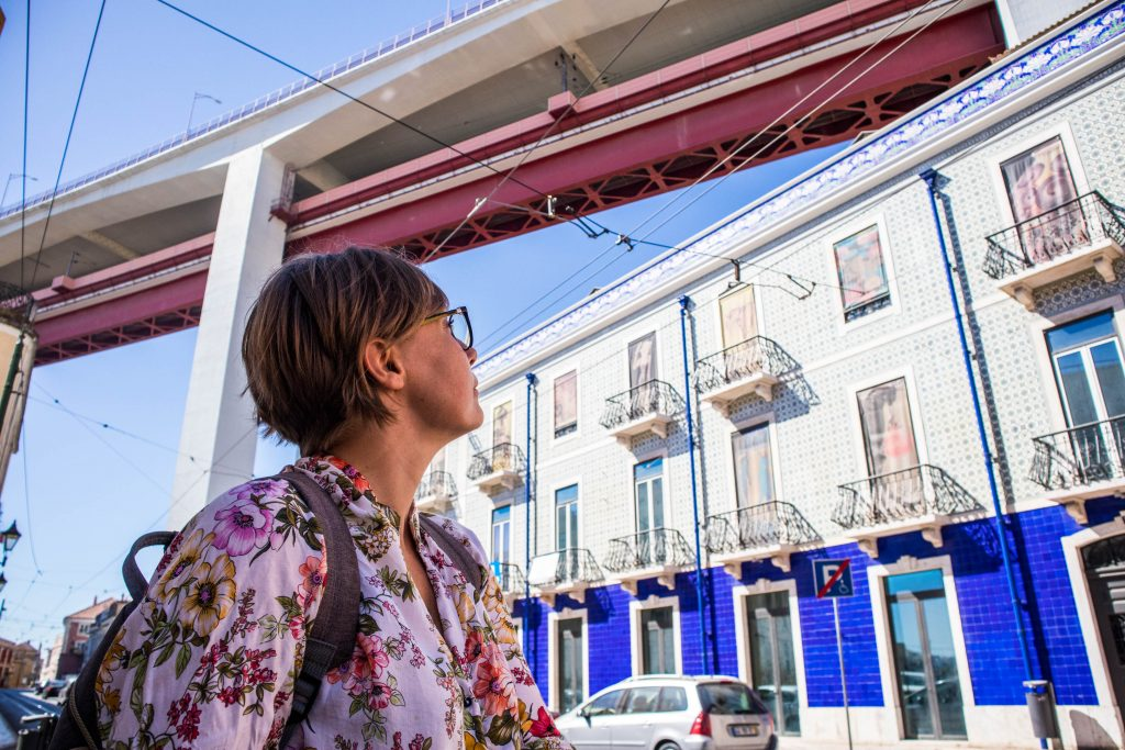 a girl looking at a colourful building in lisbon
