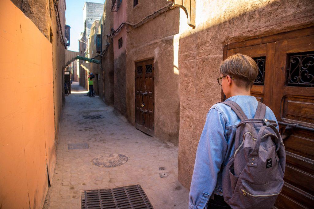 a girl in a jeans jackets walks in an alley in marrakesh