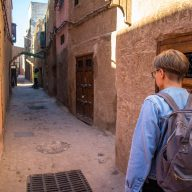 a girl in a jeans jackets walks in an alley in marrakesh