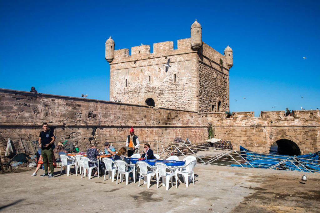 portowa restauracja w eussaouira. ludzie siedzą na zewnątrz przy murach miasta.
