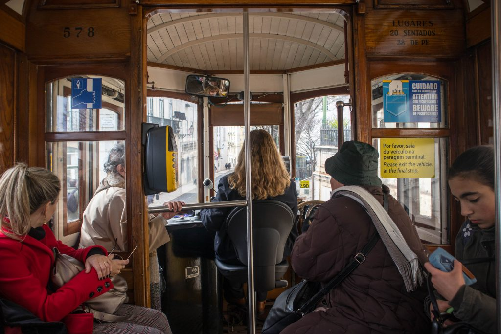 people sitting behind the driver in lisbon tram