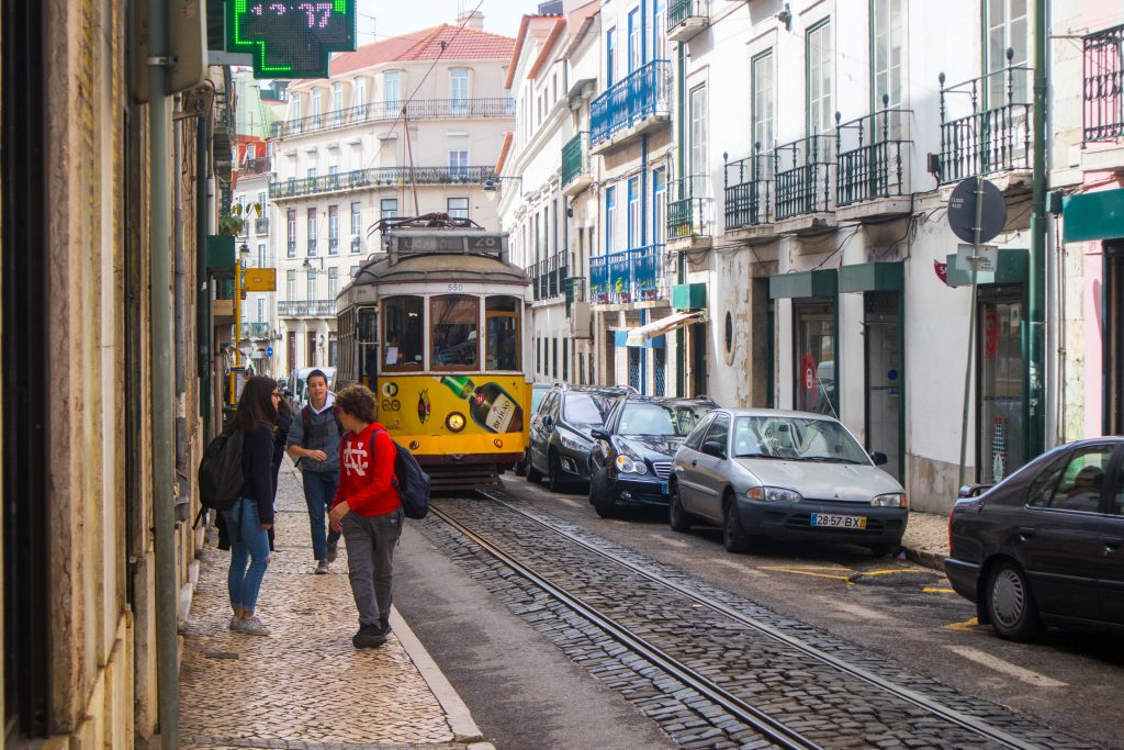 yellow tram drives through the street of lisbon passing people
