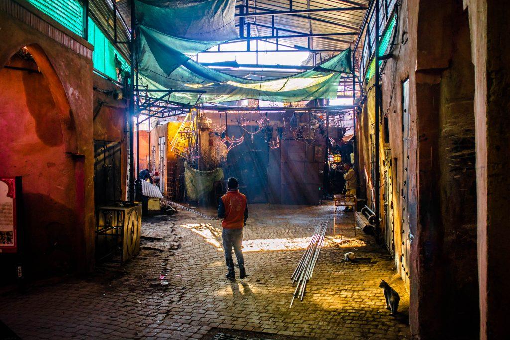 młody mężczyzna idzie ulicą marakeszu. słonce prześwituje przez dach.