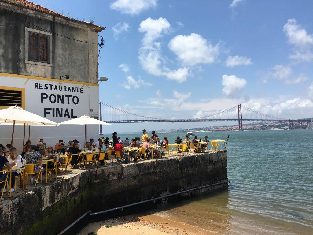 ludzie siedza przy stolikach w ponto final restuaracji na brzegu rzeki tag w tle widac most