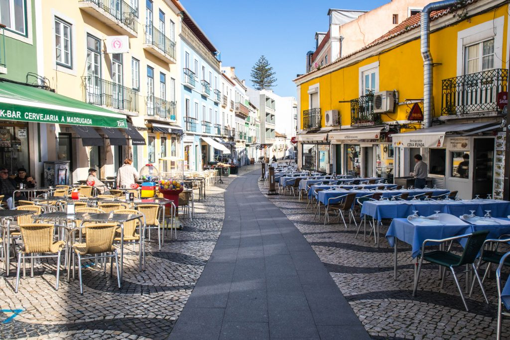 knajpki w cacilhas stoja puste ze stolikami na zewnatrz przy kolorowych domach