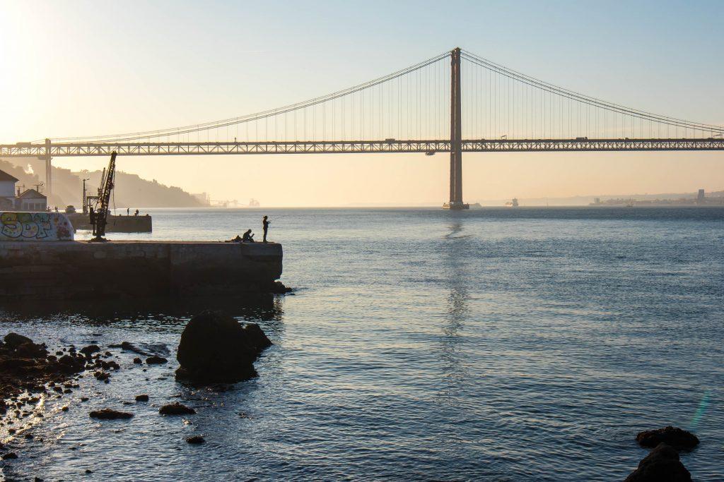 zachod slonca w almadzie kolo lizbony. w tle widac most. na pierwszym planie jest wedkarz, budynki i skaly.