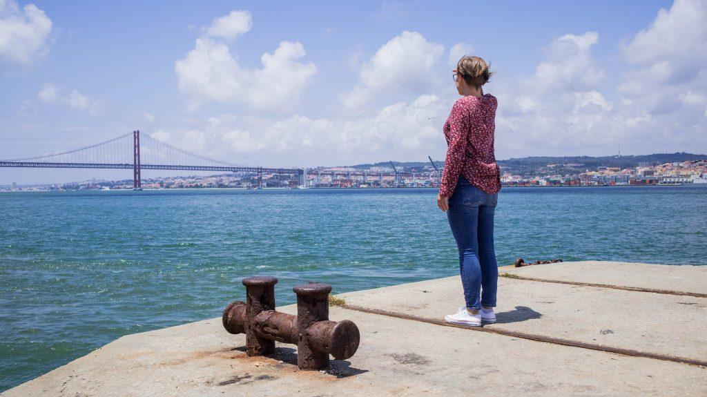dziewczyna stoi na brzegu rzeki w almadzie i patrzy na most 25go kwiietnia zaslaniajac oczy od slonca