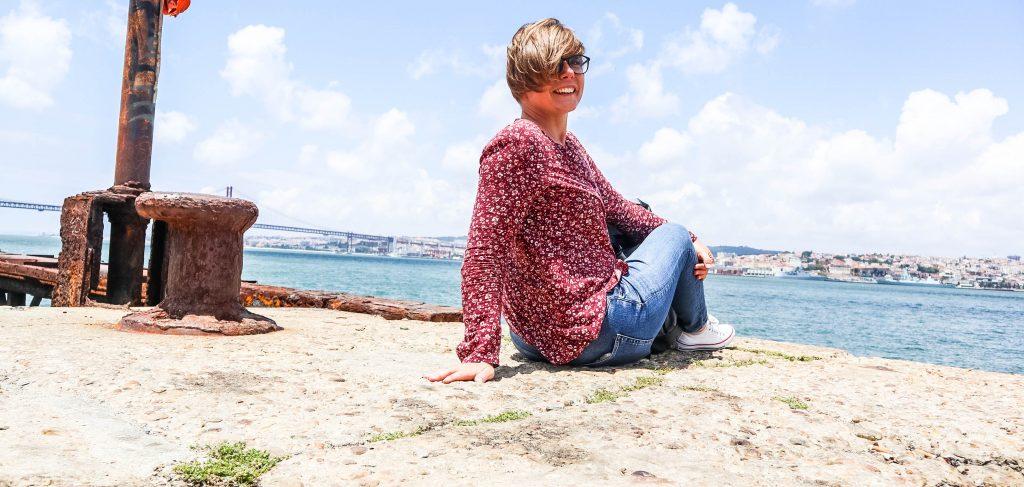 usmiechnieta dziewczyna w czerwonej koszuli siedzi na brzegu rzeki w almadzie odwrocona tylem do kamery i przodem do mostu na rzece