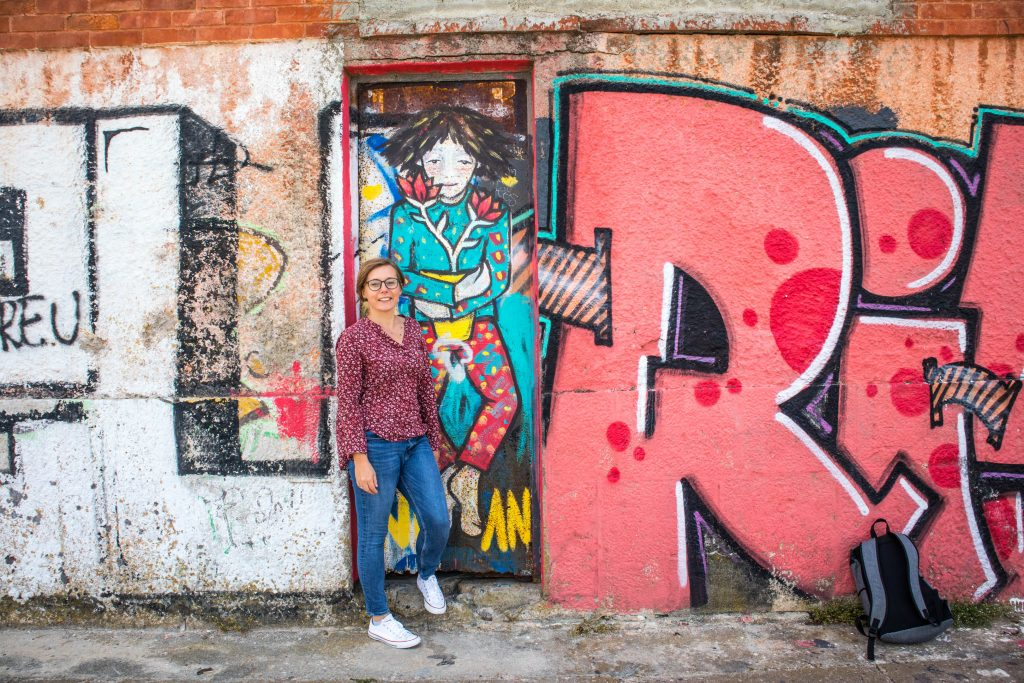 a girl stands at a grafitti wall in almada, lisbon dressed in a purple shirt and jeans smiling