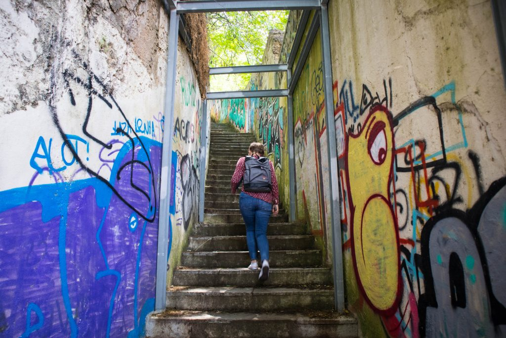 a girl in a purple shirt and jeans walks up the stairs in almada lisbon