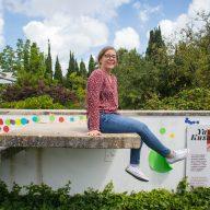 dziewczyna siedzi na murku w Jardim Botânico O Chāo das Artes z szerokim usmiechem